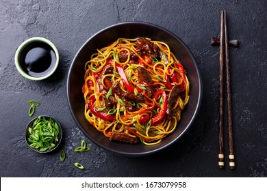 Stir fry noodles with vegetables and beef in black bowl. Slate background. Close up. Top view.