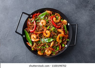 Stir fry noodles with vegetables and shrimps in black pan. Slate background. Top view.