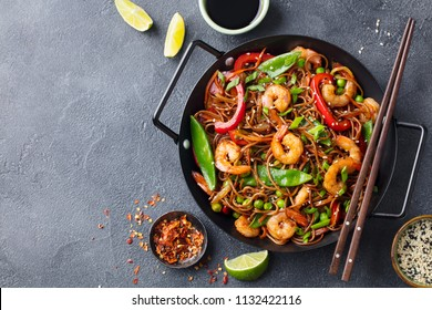 Stir fry noodles with vegetables and shrimps in black iron pan. Slate background. Top view. Copy space.