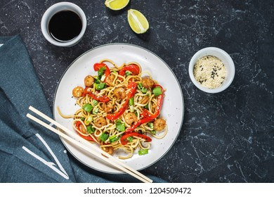 Stir fry noodles with vegetables and shrimps on dark stone background
