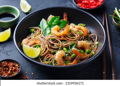Stir fry noodles with vegetables and shrimps in black bowl. Slate background. Close up.