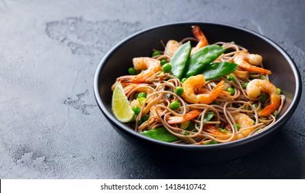 Stir fry noodles with vegetables and shrimps in black bowl. Slate background. Copy space.
