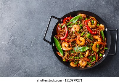 Stir fry noodles with vegetables and shrimps in black iron pan. Grey background. Copy space. Top view.