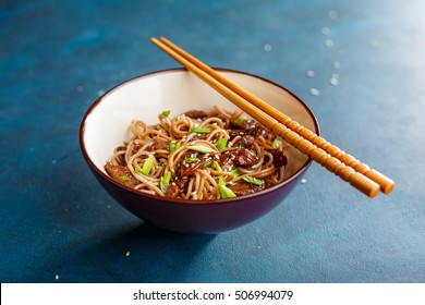 Stir fry noodles yakisoba with beef in a bowl on a blue background. Asian cuisine meal.
