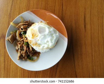 Stir fry sliced pork with basil leave and onion with fry egg on boil rice.
