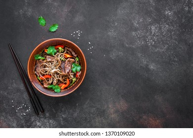Stir fry with soba noodles, beef and vegetables. Asian healthy food, stir fried meal in bowl on dark background, top view, copy space.