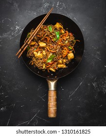 Stir fry soba noodles with chicken, vegetables in old rustic wok pan, chopsticks on black stone background, close up, top view. Traditional asian/thai meal, close up