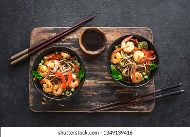 Stir fry with soba noodles, shrimps (prawns) and vegetables. Asian healthy food, stir fried meal in bowl on black background, copy space.