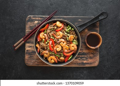Stir fry with soba noodles, shrimps (prawns) and vegetables. Asian healthy food, stir fried meal in pan on black background, top view.
