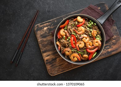 Stir fry with soba noodles, shrimps (prawns) and vegetables. Asian healthy food, stir fried meal in pan on black background, copy space.