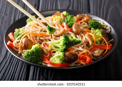 Stir Fry soba with shiitake mushrooms, broccoli, carrots, peppers close-up on a plate on the table. horizontal