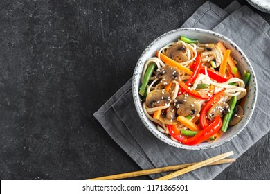 Stir fry with udon noodles, mushrooms and vegetables in bowl. Asian vegan vegetarian food, meal, stir fry over black background, copy space.