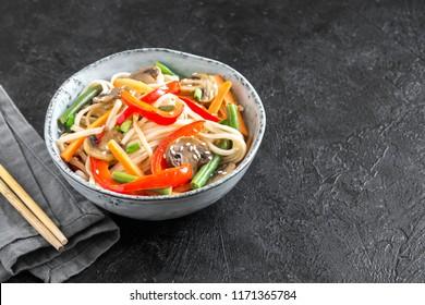 Stir fry with udon noodles, mushrooms and vegetables in bowl. Asian vegan vegetarian food, meal, stir fry over black background, copy space.
