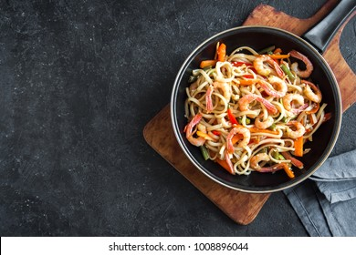Stir fry with udon noodles, shrimps (prawns) and vegetables. Asian healthy food, meal, stir fry in wok over black background, copy space.