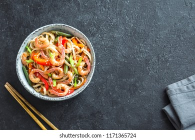 Stir fry with udon noodles, shrimps (prawns) and vegetables. Asian healthy food, meal, stir fry in bowl over black background, copy space.