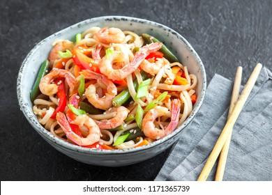 Stir fry with udon noodles, shrimps (prawns) and vegetables. Asian healthy food, meal, stir fry in bowl over black background, copy space.