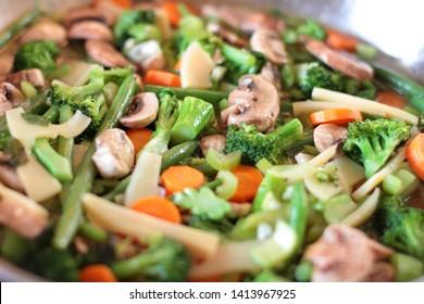 Stir fry vegetables cooking in a stainless steel pan.