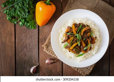 Stir frying beef with sweet peppers, green beans and rice. Top view