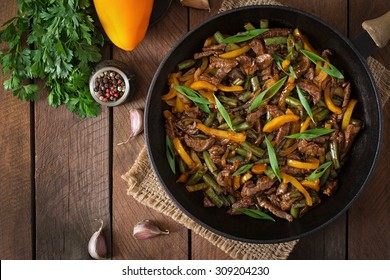 Stir frying beef with sweet peppers and green beans. Top view