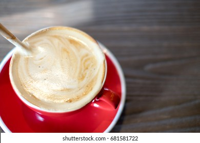 Stir latte art swirl coffee with wooden spoon in red cup on table