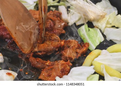 Stir in pork With sauce and vegetables in hot saucepan. At Korean Restaurant.Use a wooden spatula to stir.There is smoke coming out