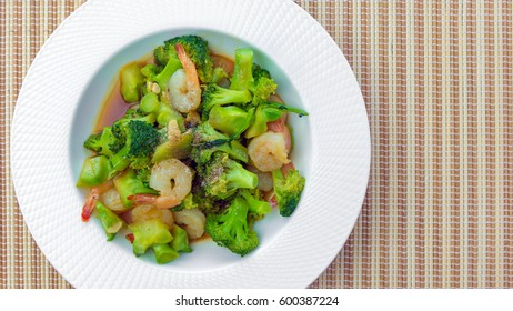 Stir-fried broccoli with shrimp in white ceramic dish.