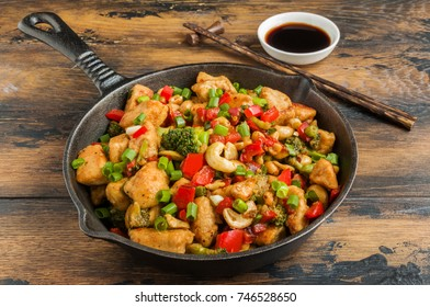 Stir-fried chicken with cashew nuts, broccoli, red bell pepper and spring onion in a black pan on the rustic wooden table.