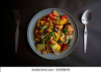 Stir-fried chicken with cashew nuts on black table.