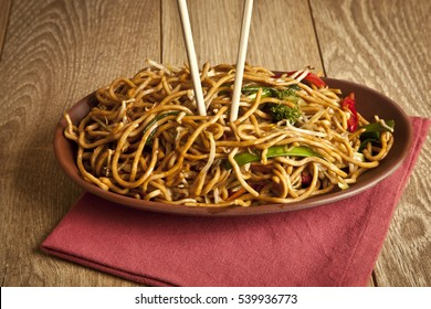 Stir-fried chinese noodles with chicken, vegetables and beansprouts on black