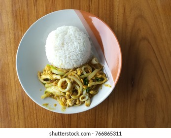 Stirfried dry curry with slice squids serve with streamed rice.