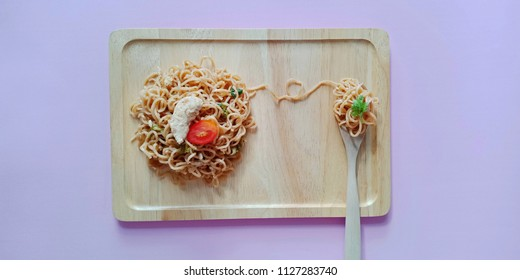 Stir-fried (dry) instant noodle (Thai MaMa) with chicken and vegetable on wooden plate and pink background. Thai food. Copy writing space.