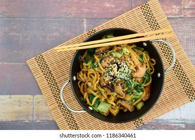 Stir-fried egg noodles with shiitake mushroom and bok choy garnish with white and black sesame seeds