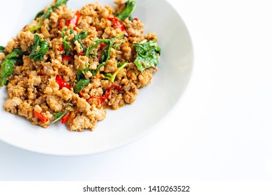 Stir-fried hot and spicy pork with holy basil on white background.