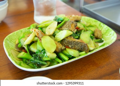 Stir-fried kale with sun-dried crispy fish on the plate