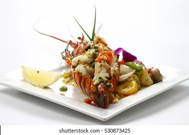Stir-fried Lobster with Butter & Garlic Sauce on white square porcelain plate Isolated on white background with shadow,Low angle Tail Side view, Luxury food. Selective Focus at front