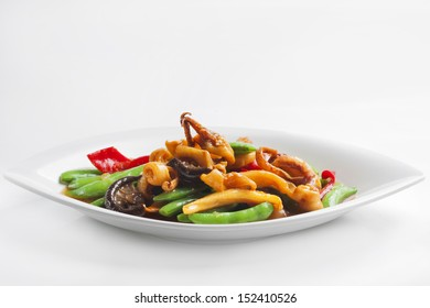 Stir-fried mixed vegetables with dried squid in dish on white background.