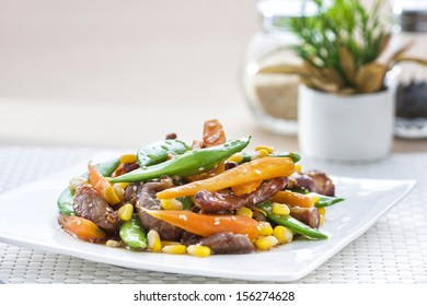 Stir-fried mixed vegetables with pork in square dish on white mat background.