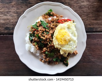 Stir-fried pork with holy basil and fried egg top view. Local thai food on wood table background.