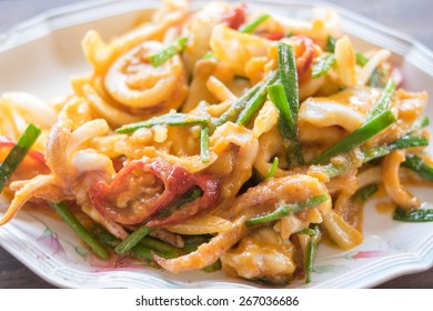 Stir-fried salted egg with squid on dish, traditional Thai food