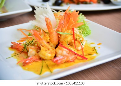 Stir-Fried Shrimp with Curry Powder in white plate on brown wood background, Thailand cuisine, Thai food