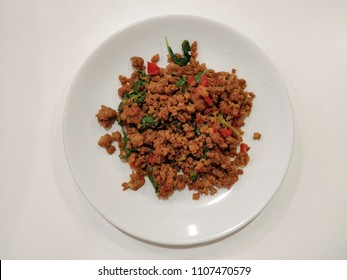 Stir-Fried Spicy Ground Pork with Holy or Thai Basil in White Plate on White Table