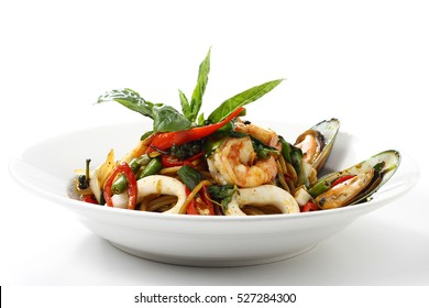 Stir-fried Spicy Spaghetti Seafood Thai Style (Spaghetti Pad Kee Mao) on White Dish, Isolated on White Background with Shadow, Front Side view. Selective Focus at the front.
