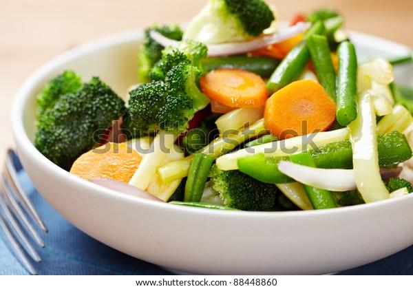 野菜炒めをボウルに入れる。青と白の豆、赤コショウ、ブロッコリー、ニンジン、ジャガイモの混合野菜サラダ。シンボル画像。おいしくて健康的なベジタリアン料理のコンセプト。 接写