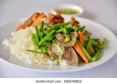 stir-fried vegetables with thai jasmine rice and fried pork in white dish