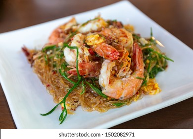 Stir-fried vermicelli with shrimp and climbing wattle vegetable. Thai spicy food.