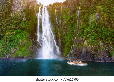 Stirling Falls at Milford Sound in South Island of New Zealand. Tourist ferry approaching Stirling Falls, the greatest waterfalls in Milford Sound, New Zealand.