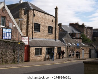 Stirling, Scotland: April 1 2021: Small social distanced queue of people in front of a brick building in Wellgreen Lane in Stirling that's used by community food larder where people can get free food