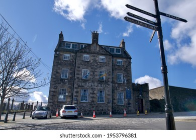 Stirling, Scotland - April 6 2021: The Portcullis pub and hotel historic building at the top of Stirling with cars parked in front of it and a pointer directory, blue sky, sunny day