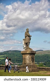 STIRLING, SCOTLAND, UK - JUNE 6,  2013 : family walking in front of a  giant stone statue of Robert the Bruce, king of Scots;  in front of Stirling castle.