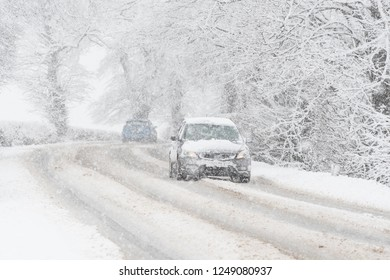 STIRLINGSHIRE, SCOTLAND, UK - 4 APRIL 2018: a car driving along a snow covered road in falling snow in Scotland